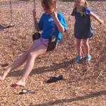 Abby & Gianna having fun on the swings.